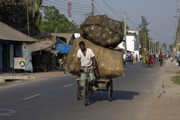 Familiar street scene in Bangladesh: man pedaling with a heavy load on the back of his bike | Bangla Pedal Power | Bangladesh