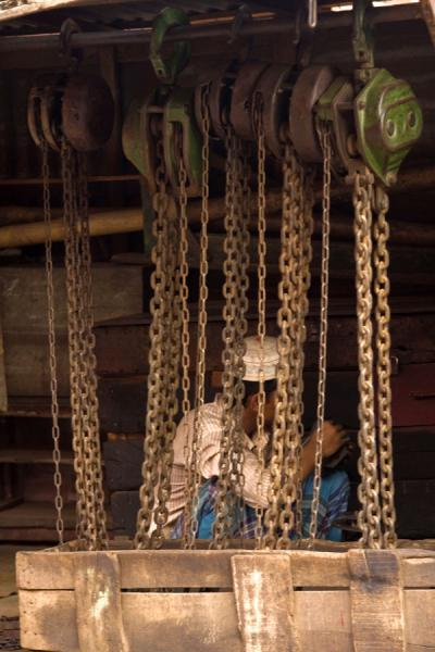 Picture of Dhaka Shipyard (Bangladesh): Man sitting behind rusty chains in the shipyard of Dhaka