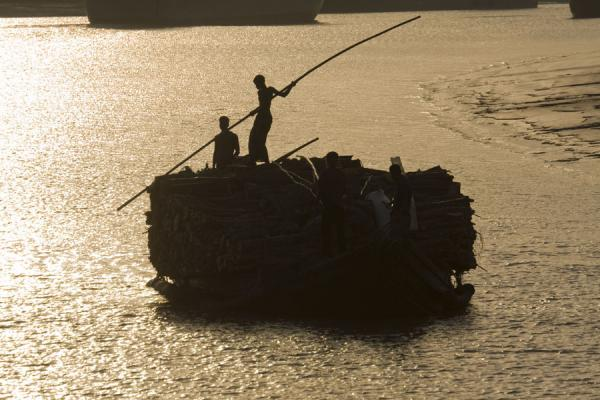 Picture of Rocket boat ride (Bangladesh): Using poles for navigation: man on his overloaded boat on a river in Bangladesh