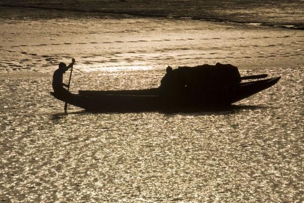 Picture of Rocket boat ride (Bangladesh): Silhouette of man and his boat on a river in southern Bangladesh