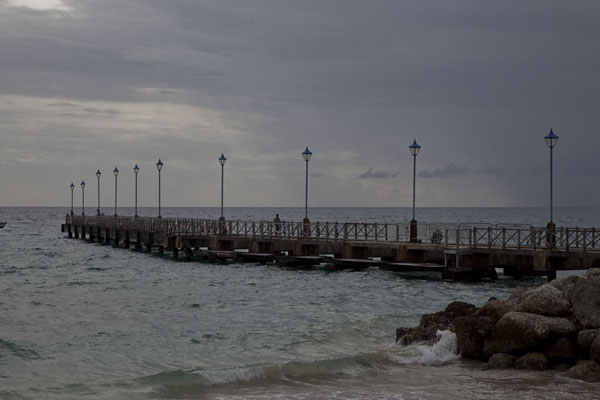 Picture of Dark skies approaching over the sea with pier of Speightstown in the foreground - Barbados - Americas