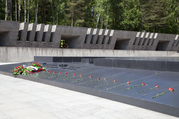 The mourning pedestal covered by flowers, with the Memory Wall in the background | Khatyn | Bielorussia