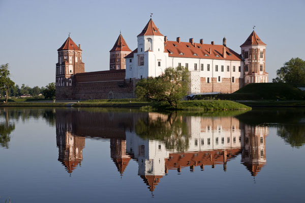 The castle of Mir reflected in the pond in the early morning | Mir Castle Complex | Belarus