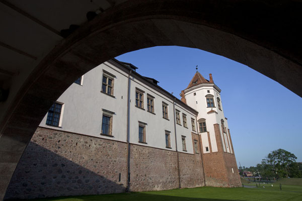 Looking at one of the towers of Mir castle seen from under an arch in the bridge | Mir Castle Complex | Belarus