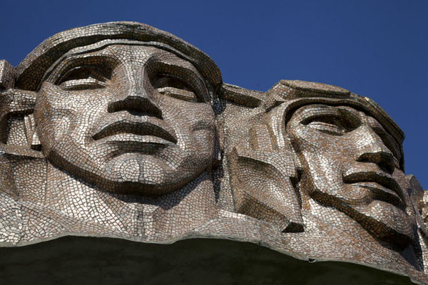 Close-up of faces of fighters sculpted on the outside of the golden circle | Mount of Glory | Belarus