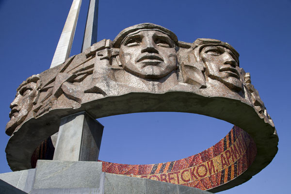 The circle with faces of soldiers and partisans has inscriptions inside | Mount of Glory | Belarus