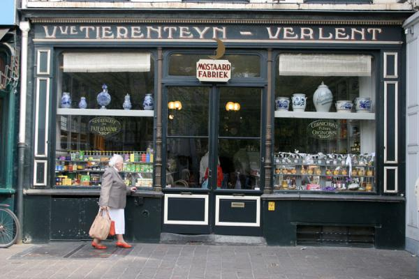 Picture of Old woman window-shopping at old shopGhent - Belgium