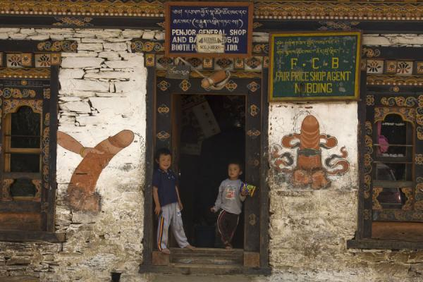 Picture of Bhutan phallic symbols (Bhutan): Bhutanese boys standing in a door opening with phalluses