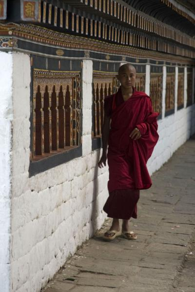 Foto van Bhutanese monk walking past prayer wheels at Thimpu DzongBhutaanse monniken - Bhutan