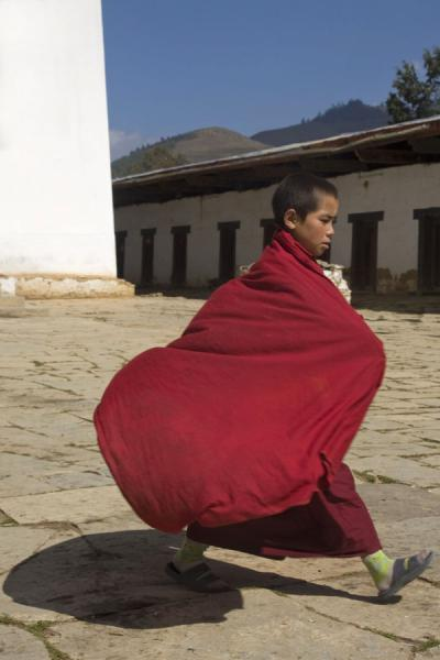 Foto van Young Bhutanese monk walking across the courtyard of Gangte GoembaBhutaanse monniken - Bhutan