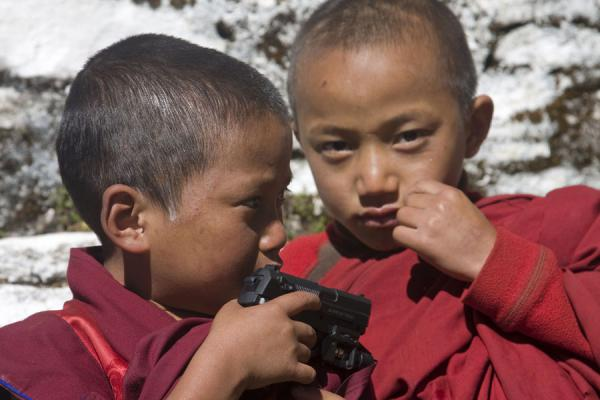 Foto van Young monk playing with ... a pistol?Bhutaanse monniken - Bhutan