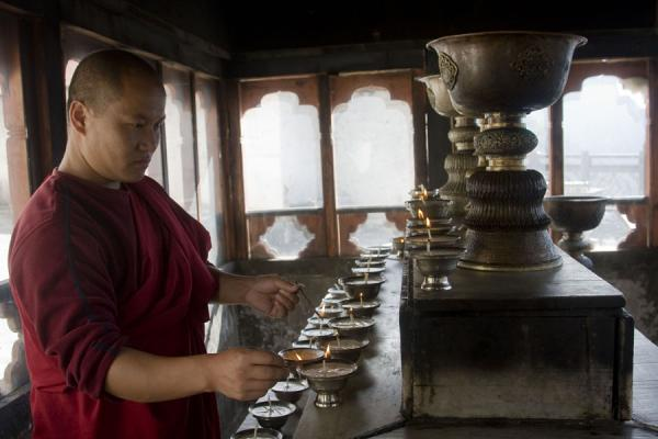 Bhutanese monk lighting butter lamps inside Cheri Monastery - 不丹