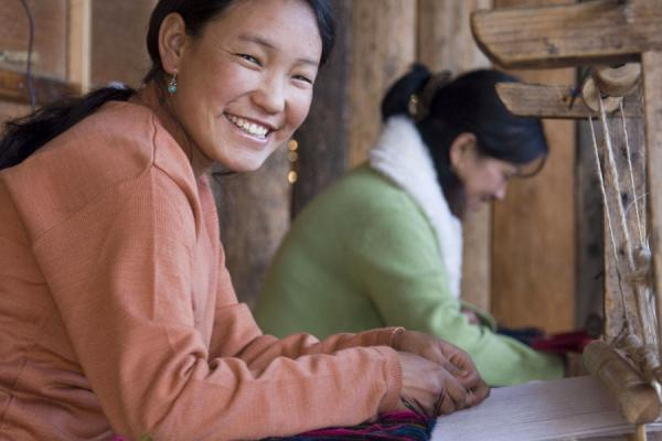 Foto van Girl weaving famous yathra, intricately woven strips of clothBhutaanse vrouwen - Bhutan