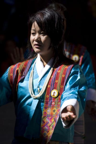 Woman performing a traditional dance in between religious dances | Bumthang Tsechu | Bhutan