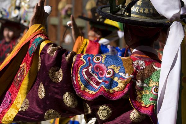 Brightly coloured clothes of dancer at Black Hat dance | Bumthang Tsechu | Bhutan