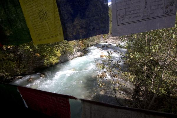 Wang Chhu river flowing under the bridge decorated with prayer flags | Cheri Monastery | Bhutan