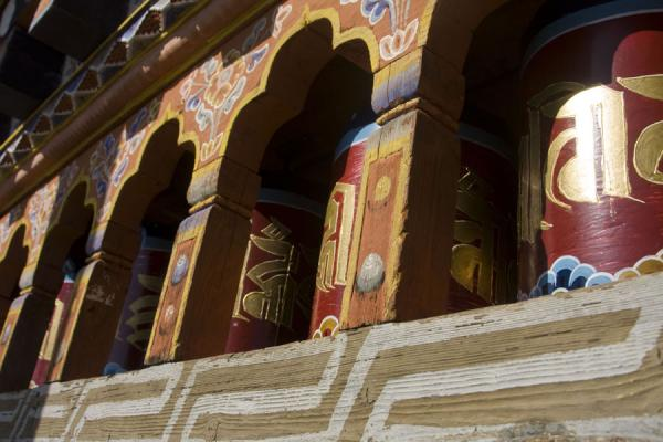 Prayer wheels in bright gold and red at Kunzangdrak | Kunzangdrak Monastery | Bhutan