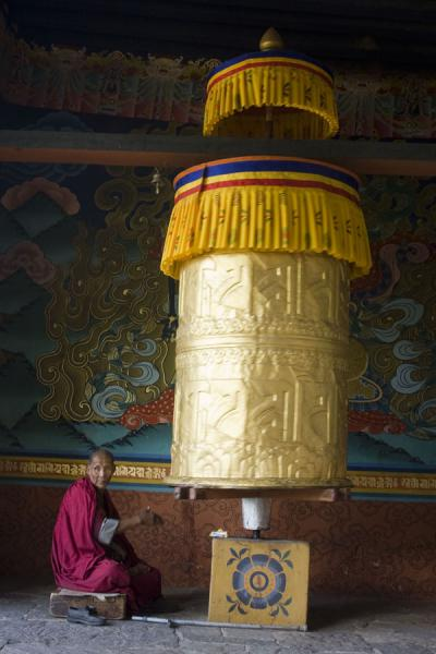 Monk turning the giant prayer wheel at the entrance | Punakha Dzong | Bhutan