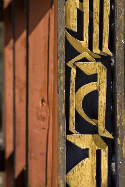 Picture of Bhutanese text on wooden balcony in Tango Monastery