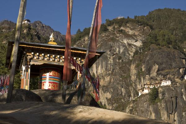 Large prayer wheel on a rock with Tiger Nest Monastery in the background | Tiger Nest Monastery | Bhutan