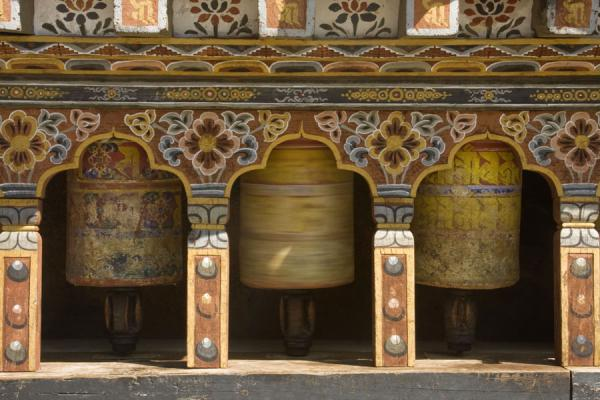 Picture of Trongsa Dzong (Bhutan): Colourful prayer wheels spinning around prayers in Trongsa Dzong