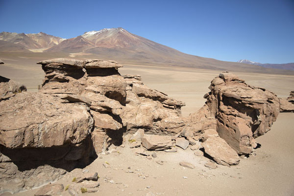 View from the top of one of the rocks with other formations and mountain in the background | Bosque de piedras de Eduardo Avaroa | Bolivia