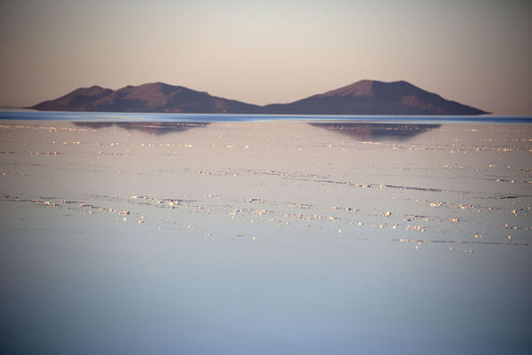Hills reflected in the quiet water of the Salar de Uyuni, the biggest mirror in the world in the wet season | Salar de Uyuni | Bolivia