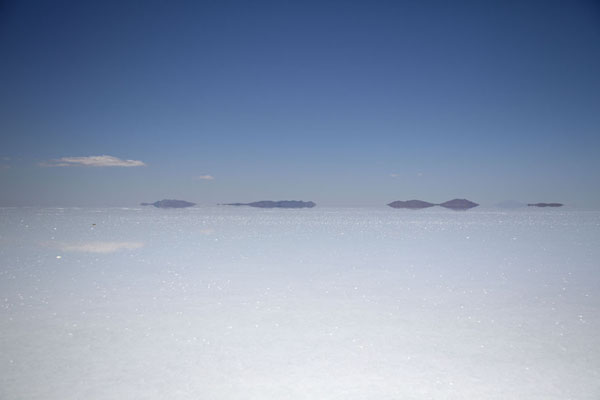 Remote islands reflected in the thin layer of water on the salt flat | Salar de Uyuni | Bolivia