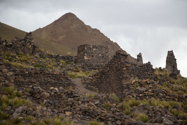 Stone walls of San Antonio de Lípez with mountain behind | Città fantasma | Bolivia