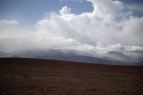 Clouds with showers sailing in over the mountains near the Laguna Colorada | Southwest Bolivia landscapes | Bolivia