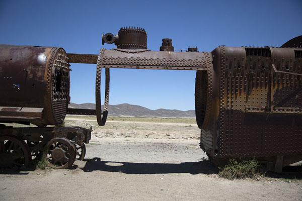 The altiplano landscape visible through the opening between two rusty train carriages | Cimitero dei treni | Bolivia