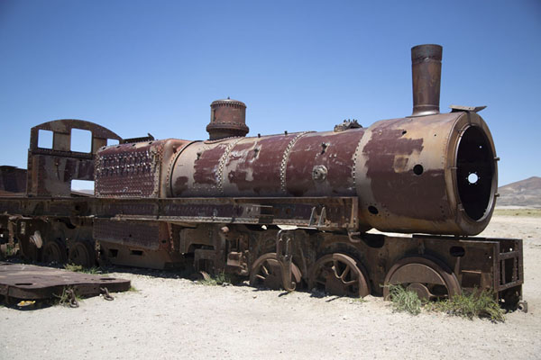 Rusty locomotive partly sunk in the ground | Train cemetery | Bolivia