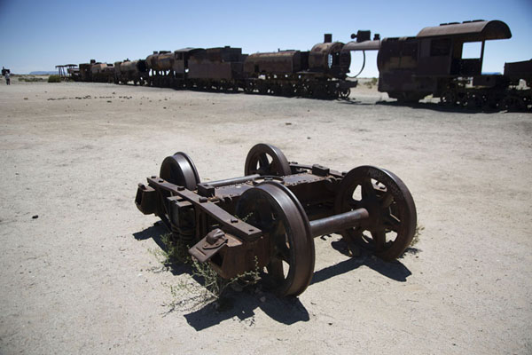 Foto di Set of wheels with train in the backgroundUyuni - Bolivia