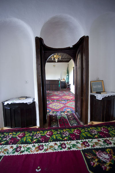 Carpets decorate the floor, and the wooden doors and ceilings are also decorated | Blagaj Tekke | Bosnia and Herzegovina