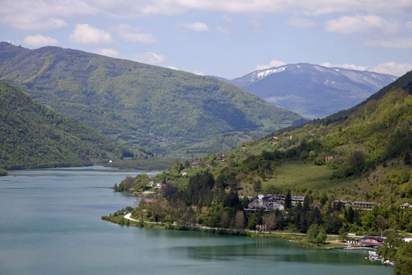 Picture of Pliva Lakes (Bosnia and Herzegovina): The shoreline of the large Pliva lake and snow-capped mountains in the distance