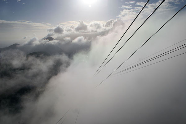 Cable car lines disappearing into the clouds between Urca and Sugarloaf mountains | Sugarloaf | Brazil