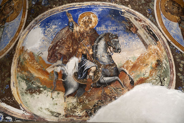 Foto van Saint George slaying the dragon, fading mural on the outside wall of the churchBachkovo - Bulgarije