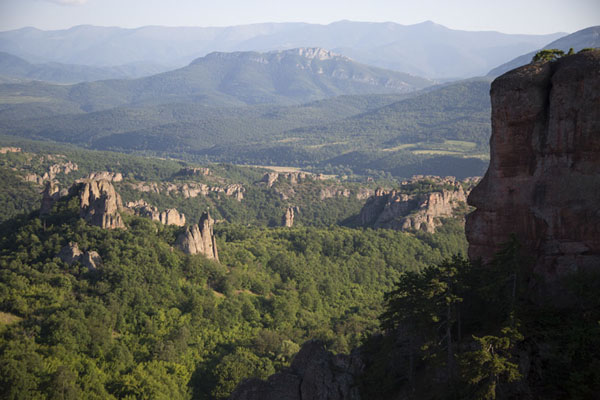 View from the backside of Belogradchik fortress with rock formations jutting out of the forest | Rocas de Belogradchik | Bulgaria