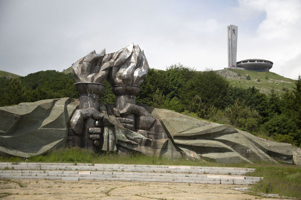 Clinched fists holding torches with the Buzludzha monument in the background | Monumento di Buzludza | Bulgaria