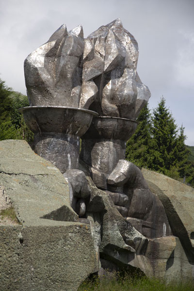 Close-up of the sculpted fists holding torches at the foot of the mountain | Monument Bouzloudja | Bulgarie