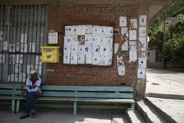 Picture of Man sitting at the post office of Pirin with death announcementsPirin - Bulgaria