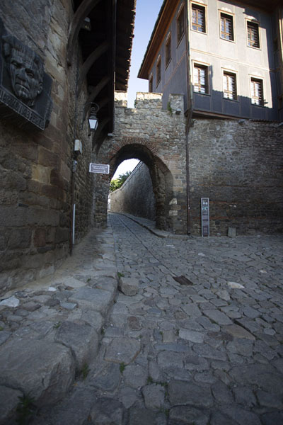 Cobble-stoned street with one of the old city gates | Cité vieille de Plovdiv | Bulgarie