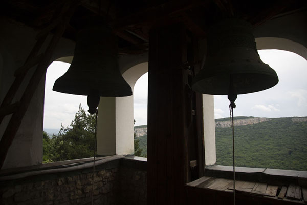 Two of the seven bells in the bell-tower, looking out over the green landscape below | Monastère de la Transfiguration | Bulgarie