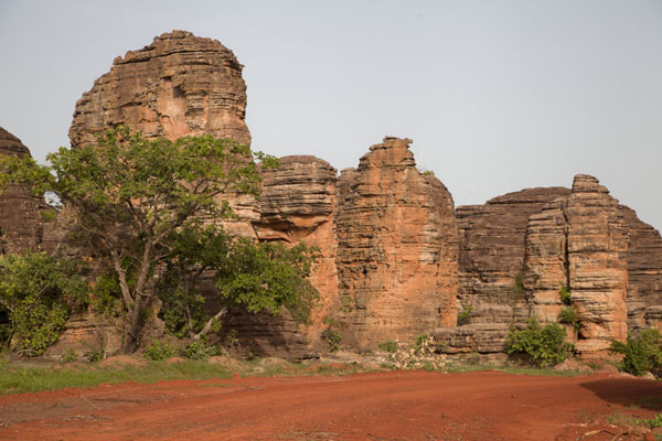 Some of the domes with the red-earth road in front | Koepelrotsen van Fabedougou | Burkina Faso