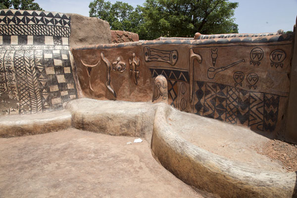 Wall with painted symbols and sculpted animals and objects in Tiébélé | Tiébélé painted houses | Burkina Faso