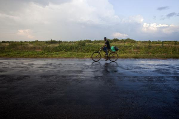 Foto di Cyclist happily taking the road after heavy rainfallGrassfields Ring Road - Burundi