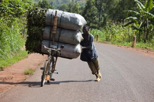 Cyclist pushing his heavily loaded bike uphill | Burundi cyclists | 薄隆地