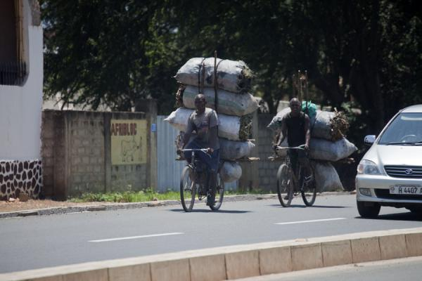 Two cyclists with heavily loaded bikes on the boulevard in Bujumbura | Burundi cyclists | Burundi