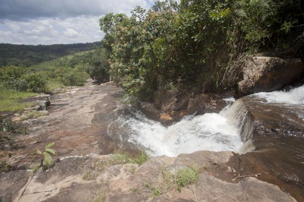Water tumbling down over the rocks at the highest level waterfall | Chutes de la Karera | Burundi