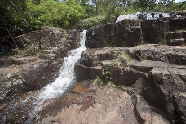 Water rushing down the rocks towards yet another waterfall | Chutes de la Karera | Burundi